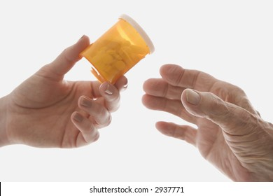 Close-up of mid-adult Caucasian female's hand handing medication bottle to elderly Caucasian male hand.