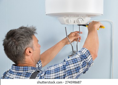 Close-up Of Mid-adult Male Plumber Installing Water Heater