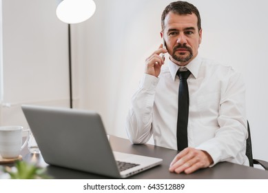 Close-up of a middle-aged financialmanager sitting at his workstation in front of computer and laptop while on business phone conversation.