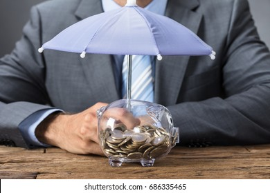 Closeup midsection of businessman sheltering transparent piggybank with umbrella at table