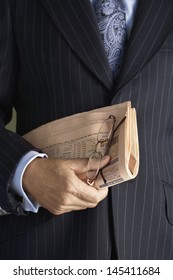 Closeup midsection of a businessman in suit holding glasses and newspaper
