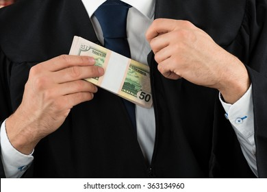 Closeup midsection of corrupt judge putting dollar bundle in pocket