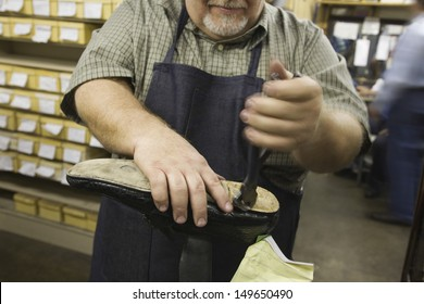 Closeup midsection of a man working at a traditional shoemaker workshop