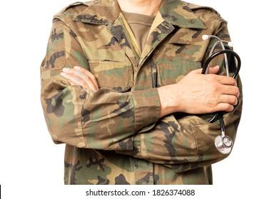 Nahaufnahme eines Militärarztes mit einem Stethoskop seiner Hand. Der Mann trägt Tarnmagen, die auch ACU genannt werden, und hat seine Arme gekreuzt.