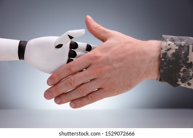Close-up Of Military Man Shaking Hands With Robot Against Gray Background