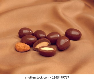 Closeup of milk chocolate covered almonds with cut open one, and raw almond on beige silk background.