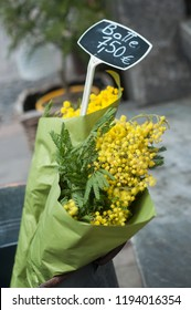 "closeup of mimosa bouquet at the florist in the street with text in french ""botte, 7,50 euros"" traduction in english (bouquet, 7,50 euros)"