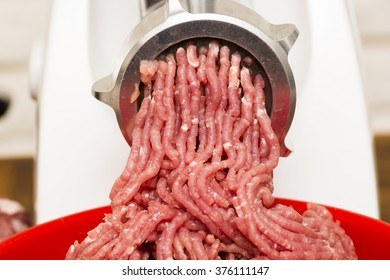 Closeup of minced meat coming out from grinder. Healthy homemade minced meat