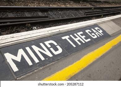 Closeup of Mind the Gap Platform Sign at Railroad Station on Diagonal Tilt