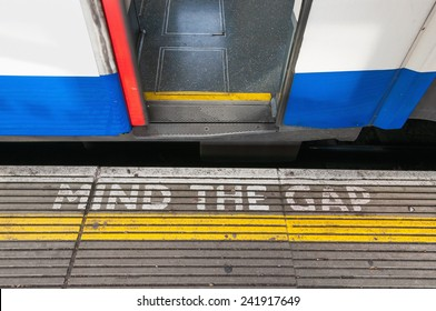 Closeup of mind the gap sign on a platform edge with open train door
