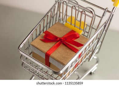closeup mini shopping cart with gift box