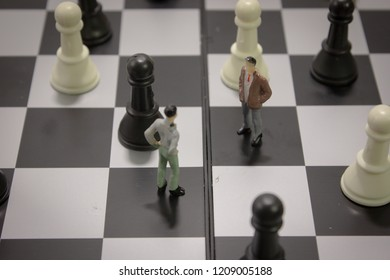 Closeup miniature businessman negotiate for cooperation on chess board with chess.