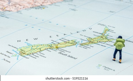 closeup of miniature figurine of young traveler standing on big map next to New Zealand islands