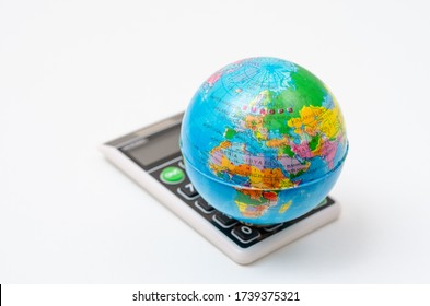 Close-up of miniature globe on a handheld calculator which represents the global economy .