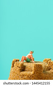 closeup of a miniature man in swimsuit relaxing on the top of a sandcastle, against a blue background with a large blank space on top