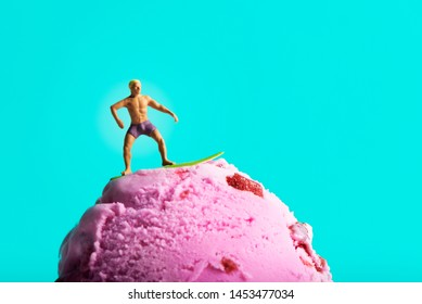 closeup of a miniature man in swimsuit surfing on a strawberry ice cream ball, against a blue background with some blank space