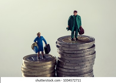 closeup of a miniature woman and a miniature man on the top of two different piles of euro coins, the man on the highest pile and the woman on the shortest pile, to depict the gender pay gap