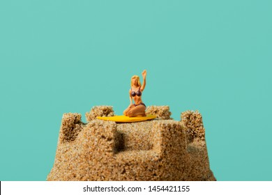 closeup of a miniature woman in swimsuit, kneeling on a surfboard, on the top of a sandcastle, against a blue background with a large blank space on top