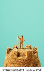 closeup of a miniature woman in swimsuit, standing next to a surfboard, on the top of a sandcastle, against a blue background with some blank space on top