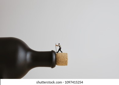 Closeup of a miniature worker opening a bottle.
