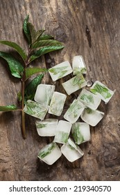 Close-up of mint ice cubes on a wooden table.