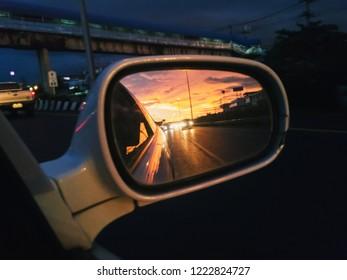 Close-up mirror, car side, evening light.