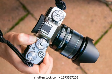 Closeup of a mirrorless camera body with lens held by a person hand