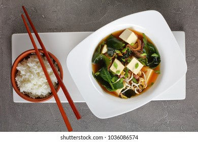 close-up of miso soup served in a white bowl with chopsticks and steamed rice, view from above