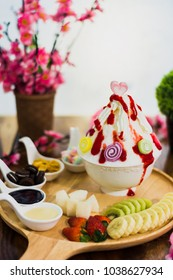 Closeup mix fruit Bingsu on tray, Bingsu or Bingsoo, Korean shaved ice dessert with sweet toppings and fruits and varieties with ingredients