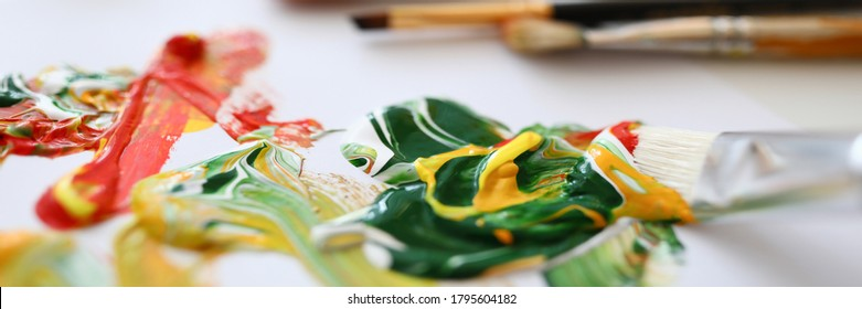 Close-up of mixed yellow green and red paints. Creamy oil paints on palette. Painter equipment for work. Different paintbrushes. Creativity flow. Artistry concept