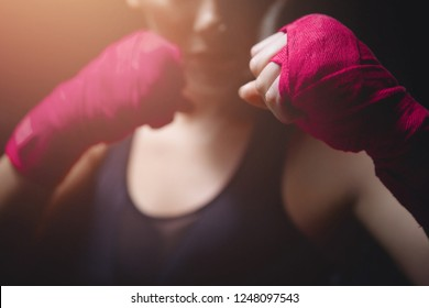 Close-up of MMA Girl holding fists pink Boxing bandages to protect her fingers in fight. Concept women self-defence