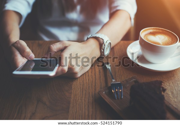 Close-up of mobile phone in woman's hands texting message, sitting in cafe with cup of coffee and cake