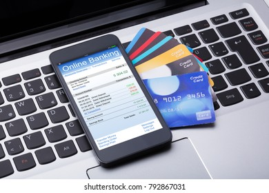 Close-up Of Mobilephone With Online Banking App And Credit Cards On Computer Keyboard