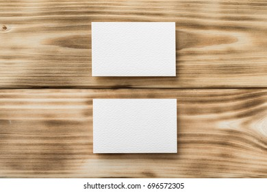 Closeup mockup of two white blank horizontal business cards at light natural wooden background.