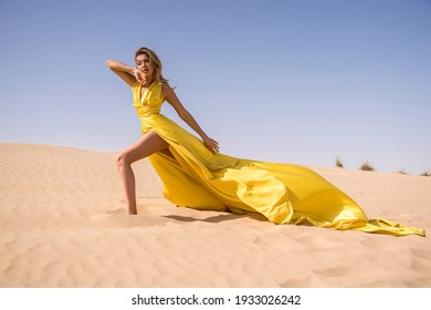 Close-up model face portrait of young Beautiful sexy blonde  woman tanned skin face cosmetic makeup wear silver  accessories, walking in the sand of desert dunes. Hot country, travel.Dress in gold