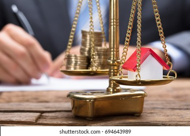 Closeup of model home and coins on golden weighing scale with businessman in background