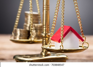 Closeup of model home and coins on golden weighing scale against gray background
