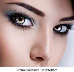 Closeup model's face of young woman with beautiful blue eyes with long eyelashes