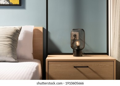 Closeup of modern black metal edison bulb lamp on wooden bedroom night table in contemporary style gray room interior with pine wood bed and white cotton bedlinen