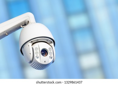 Close-up of modern CCTV camera with business buildings in the background