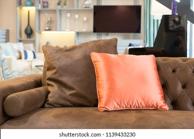 Closeup of modern dark brown couch and orange colored pillow. Flat television and trinkets background. Contemporary interior of modern designed Living room with part of sofa in sunny day.