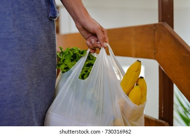 Closeup of modern elegant stylish adult woman buyer holding shopping purchase bag on the street background. Busy consumerism spending lifestyle