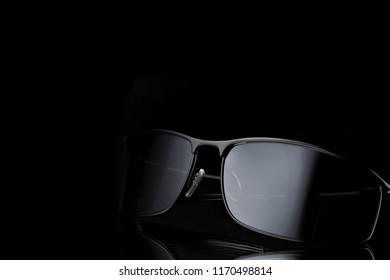 Closeup of modern elegant sunglasses shining in darkness on black background.