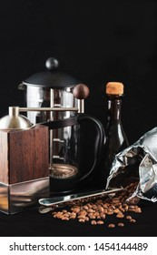 closeup of modern hand-operated coffee grinder made of wood and steel standing on black background next to transparent percolator of glass and coffee beans poured out of coffee bag