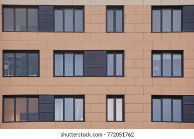 Closeup of a modern skyscraper of square design forms with lots of windows. The facade of the building is brown and beige .
