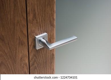 Close-up of modern steel door handle on interior door. Dark oak and frosted glass.