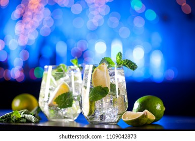 Closeup of mojito cocktails on a bar lights background. Copy space.