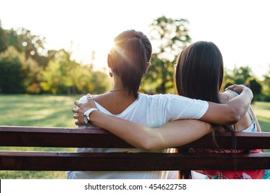 Closeup of mom and daughter embracing on a park bench at sunset