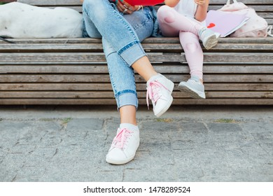 Closeup of mom and her daughter sitting on a bench. Love of mother and daughter. Mothers day.
