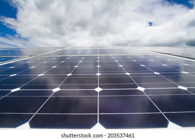 Closeup of the mono-crystalline photovoltaic cells and reflection of the cloudy sky